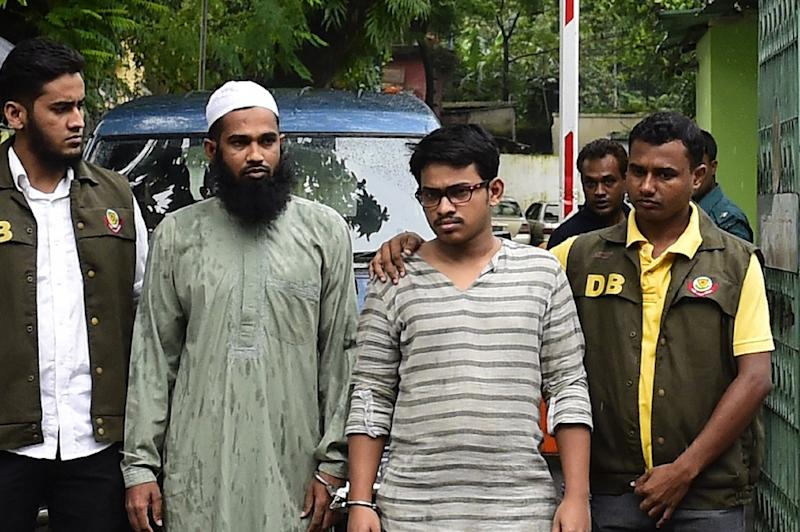 Bangladesh police officials parade suspects Masud Rana (2L) and Sad Al Nahin (2R) in Dhaka on August 14, 2015 after their arrest in connection with the murder of secular blogger Niloy Chakrabarti