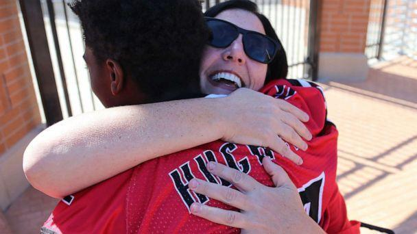 PHOTO: Dana Gendreau hugs the Hughes football player as they get off the bus before there game on Oct. 6, 2019. (Tony Tribble, Cincinnati Enquirer via Imagn)