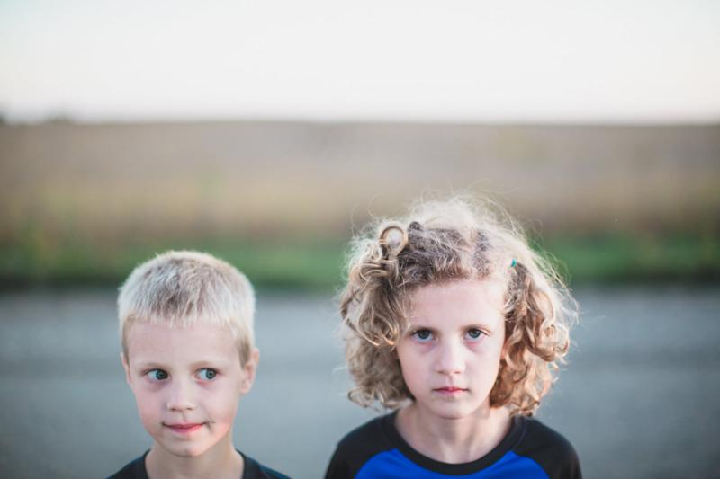 Close up portrait of a boy and girl standing side by side. Girl with curly hair looks sternly into the camera while blond boy looks at her with side eyes and a mischievous expression.