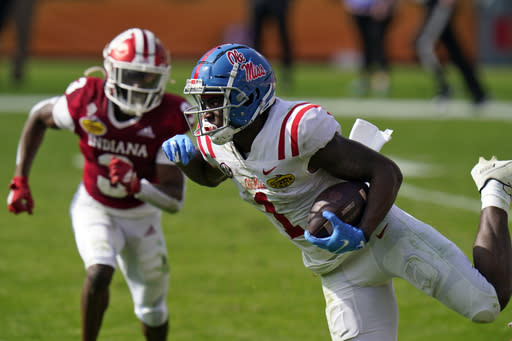 Mississippi wide receiver Jonathan Mingo (1) eludes Indiana defensive back Tiawan Mullen on a run during the first half of the Outback Bowl NCAA college football game Saturday, Jan. 2, 2021, in Tampa, Fla. (AP Photo/Chris O'Meara)
