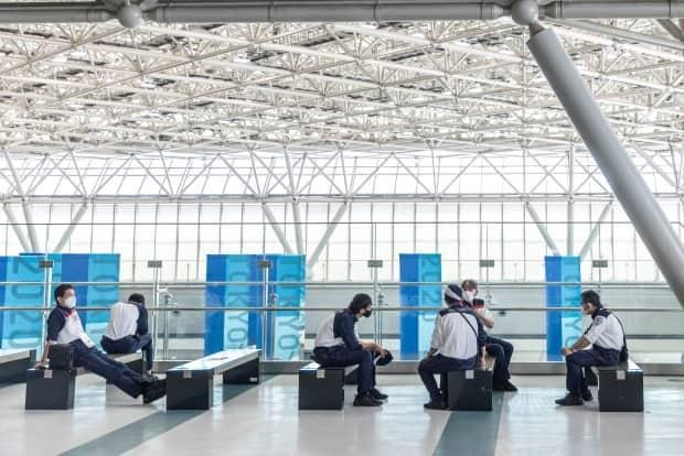 Security guards sit in the IBC/MPC Tokyo International Exhibition Centre ahead of the 2020 Olympic Games on July 20 in Tokyo. Set to begin on Friday, the event was touted as safe and secure by organizers, but has so far been plagued by COVID-19 infections. (Maja Hitij/Getty Images - image credit)