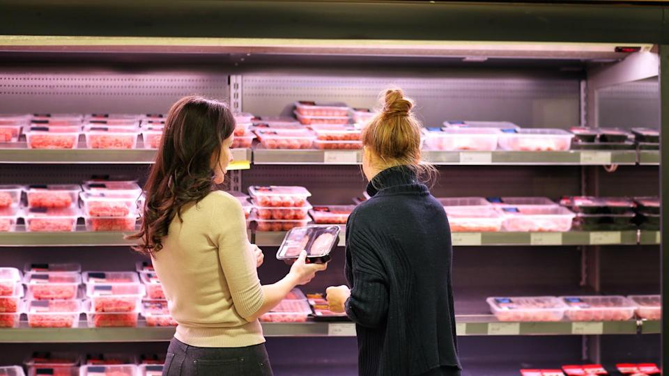 Women purchasing a packet of meat at the supermarket.