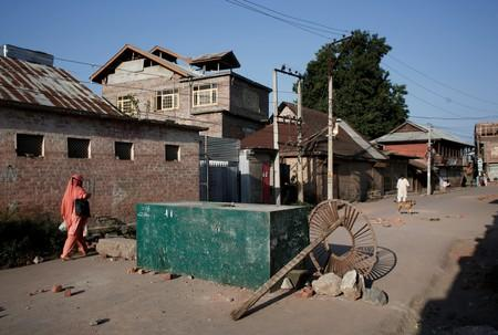 A Kashmiri woman walks past a blockade put up by residents to prevent Indian security force personnel from entering their neighborhood during restrictions, in Srinagar