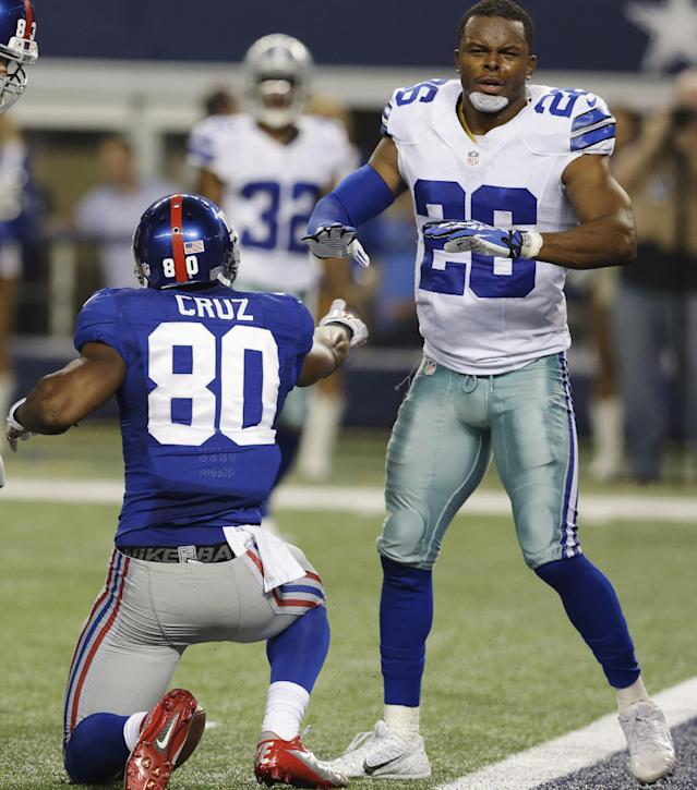 New York Giants wide receiver Victor Cruz (80) celebrates his 18-yard touchdown as Dallas Cowboys safety Will Allen (26) disagrees with the call during the second half of an NFL football game, Sunday, Sept. 8, 2013, in Arlington, Texas. (AP Photo/LM Otero)