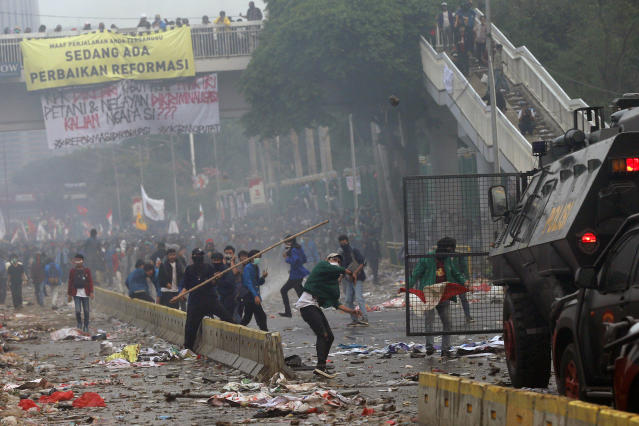 Student protesters use sticks to attack riot police during clash at a outside parliament in Jakarta, Indonesia, Tuesday, Sept. 24, 2019. Thousands of students have staged rallies across Indonesia against new law that considered has crippled means in fighting the country's endemic corruption. (AP Photo/Tatan Syuflana)