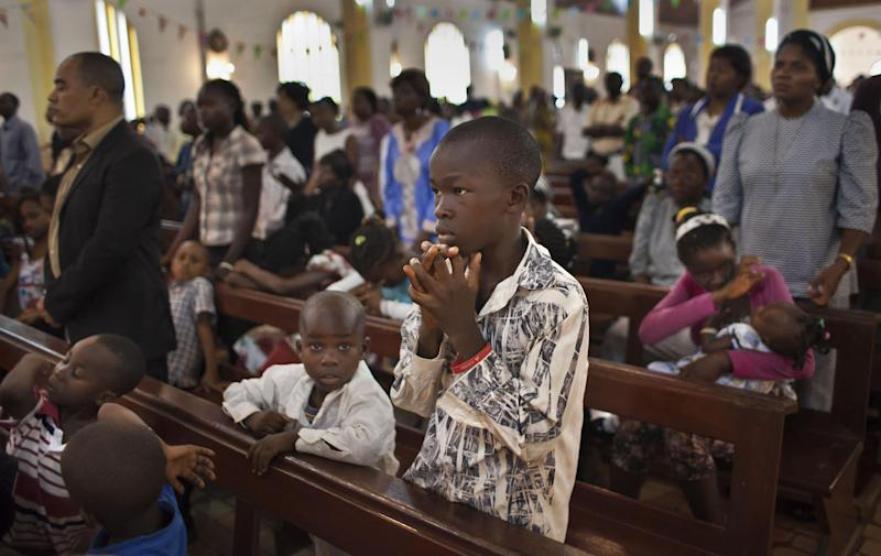 A young boy prays during morning mass at the Notre Dame Cathedral of the Immaculate Conception in Bangui, Central African Republic Sunday, Jan. 6, 2013. Rebels in Central African Republic seized control of another town on Saturday, just days before they are to begin negotiations with the government, casting doubt on the possible success of the talks. (AP Photo/Ben Curtis)