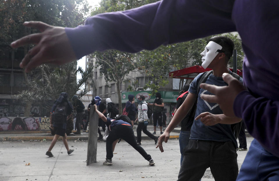 A mask demonstrator clash with the police during an anti-government protest in Santiago, Tuesday, Nov. 5, 2019. Chileans have been taking to the streets and clashing with the police to demand better social services and an end to economic inequality, even as the government announced that weeks of demonstrations are hurting the country's economic growth. (AP Photo/Esteban Felix)