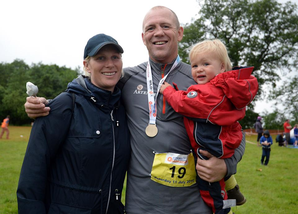 Zara Phillips in a black cap and jacket with Mike Tindall holding their daughter Mia