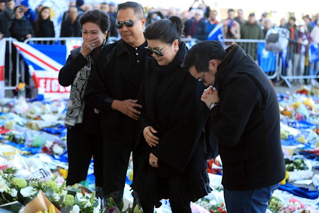 <p>Aiyawatt Srivaddhanaprabha lays a wreath in memory of his father with his mother Aimon (second right). Mike Egerton/PA Wire </p>