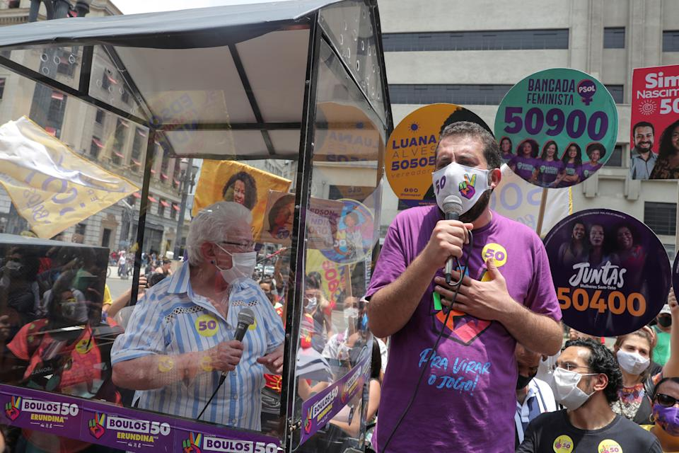 """Mayor candidate Guilherme Boulos speaks as his vice-mayor candidate Luiza Erundina, 85, participates from inside the """"cata voto"""" (Vote Catcher), a car with a plastic booth to protect herself from the coronavirus disease (COVID-19) during the campaign in Sao Paulo, Brazil November 13, 2020. REUTERS/Amanda Perobelli"""