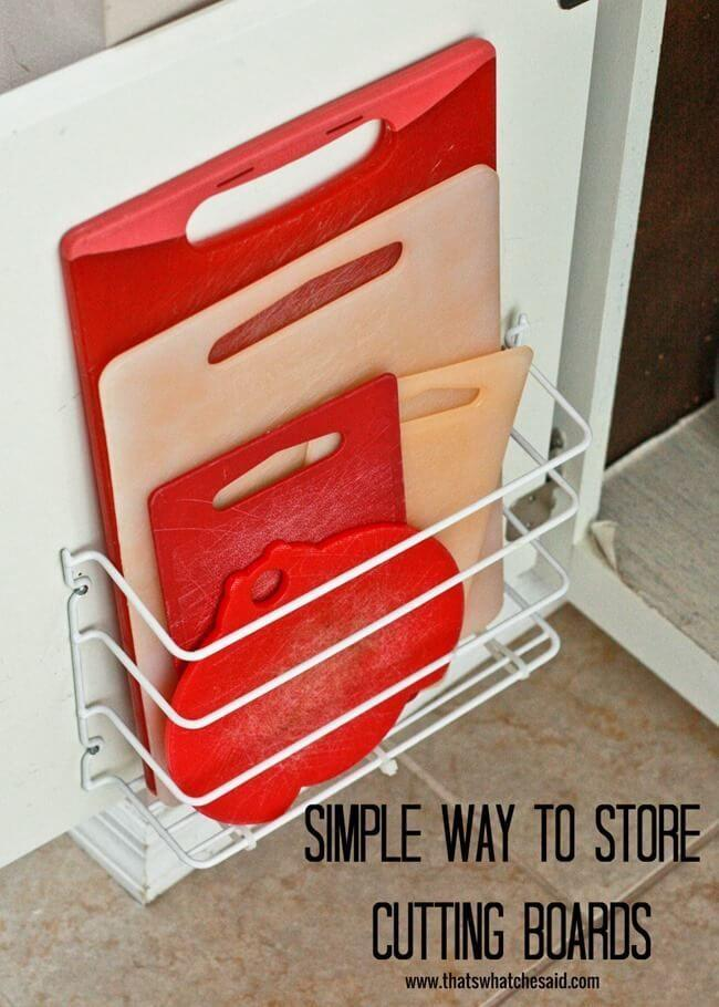"""<p>A wire bin placed on the back of your cabinet door creates a """"pocket"""" for holding the many cutting boards that normally take up space on shelves. (Just make sure you're cleaning them the right way before putting them away.)</p><p><a href=""""http://www.thatswhatchesaid.net/cutting-board-storage/"""" rel=""""nofollow noopener"""" target=""""_blank"""" data-ylk=""""slk:See more at That's What Che Said »"""" class=""""link rapid-noclick-resp""""><em>See more at That's What Che Said »</em></a></p>"""