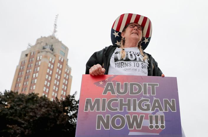 A supporter of former U.S. President Donald Trump holds a sign outside the Michigan State Capitol to demand an audit of 2020 election votes, in Lansing, Michigan, U.S. October 12, 2021. (Rebecca Cook/Reuters)
