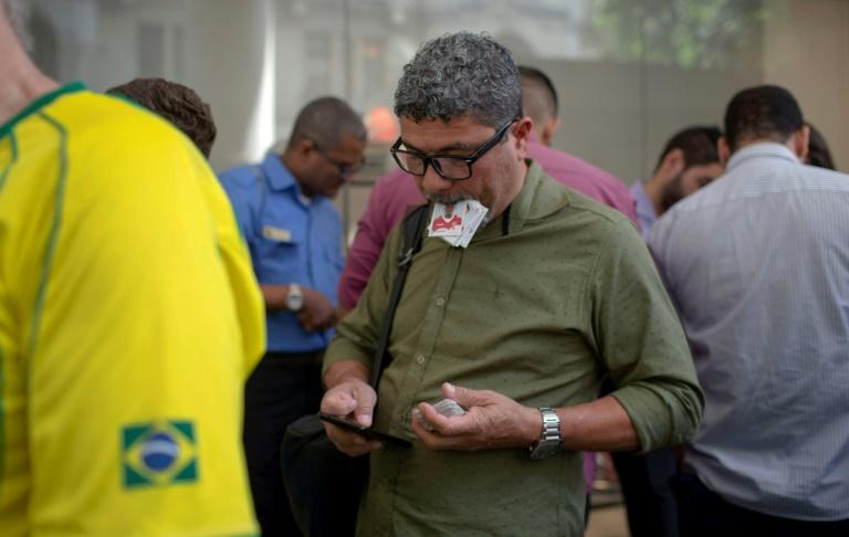 Dozens of adults huddle at the makeshift Panini sticker trading marketplaces in Rio, clutching a wad of cards they hope to swap and a list of the ones they need