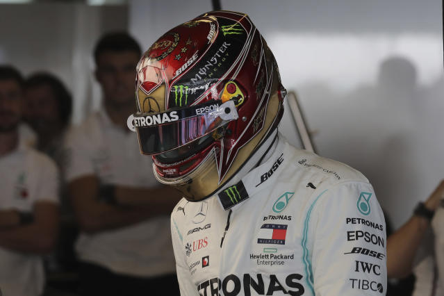 Mercedes driver Lewis Hamilton of Britain puts on his helmet during the first free practice at the Yas Marina racetrack in Abu Dhabi, United Arab Emirates, Friday, Nov. 29, 2019. The Emirates Formula One Grand Prix will take place on Sunday. (AP Photo/Hassan Ammar)