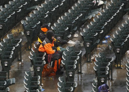 A pair of fans sits through the second rain delay at Coors Field as play was suspended in the fourth inning of a baseball game between the New York Yankees and Colorado Rockies in Denver, Thursday, May 9, 2013. (AP Photo/David Zalubowski)