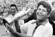 FILE - In this July 10, 1971, file photo, Lee Trevino displays his trophy as runner-up Liang-Huan Lu, background, of Taiwan, looks on at the British Open Golf Championship at the Royal Birkdale in Southport, England. Fifty years ago, Trevino won the U.S. Open, Canadian Open and British Open in the span of one month. (AP Photo/File)