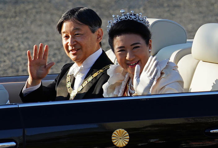 Japanese Emperor Naruhito, left, and Empress Masako, right, wave during the royal motorcade in Tokyo, Sunday, Nov. 10, 2019. (AP Photo/Eugene Hoshik