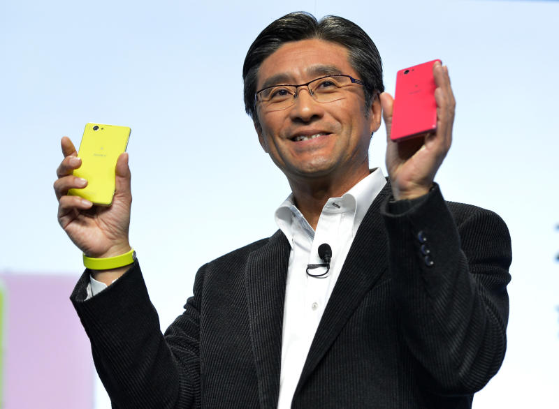 Kunimasa Suzuki, executive vice president, Sony Corporation and president and chief executive officer of Sony Mobile Communications, unveils the new Sony EXPERIA Z1 Compact in lime and pink colors during the Sony news conference at the International Consumer Electronics Show Monday, Jan. 6, 2014, in Las Vegas. The smaller phone has the same features as the ZPERIA Z1(AP Photo/Jack Dempsey)
