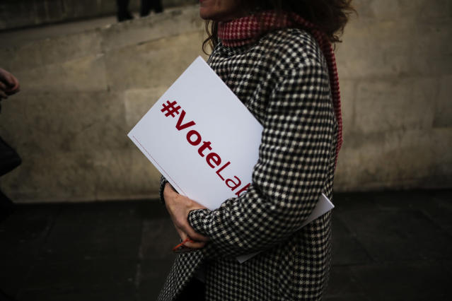 <p>A woman walks over the London Bridge carrying a placard, in London, Tuesday, June 6, 2017. Britain will hold a general election on June 8. (Photo: Markus Schreiber/AP) </p>