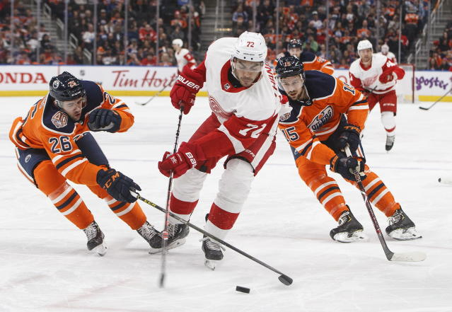 Detroit Red Wings' Andreas Athanasiou (72) is cased by Edmonton Oilers' Brandon Manning (26) and teammate Alex Petrovic (15) during first period NHL action in Edmonton on Tuesday, Jan. 22, 2019. (Jason Franson/The Canadian Press via AP)