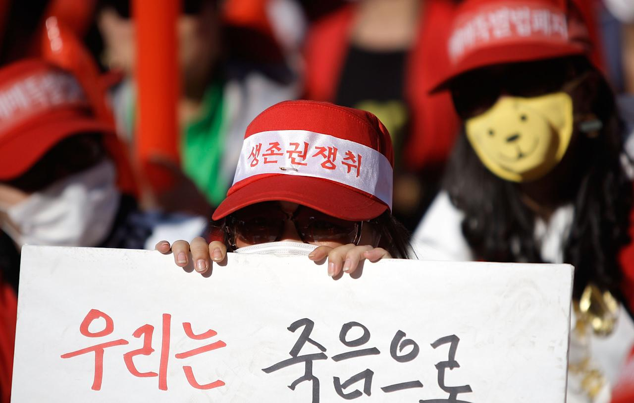 SEOUL, SOUTH KOREA - SEPTEMBER 22:  South Korean prostitutes hide their identities as they participate in a rally on September 22, 2005 in Seoul, South Korea. Prostitutes rallied against government law aimed at the sex industry. The government began enforcing new laws seven year ago to target human traffickers, pimps and prostitutes. Prostitutes will rallied against government law aimed at the sex industry. Nearly seven years after tough laws began driving thousands of South Korean prostitutes out of business, sex workers of the red-light district are fighting back, spurred by what they say is an unprecedented campaign of police harassment.  (Photo by Chung Sung-Jun/Getty Images)