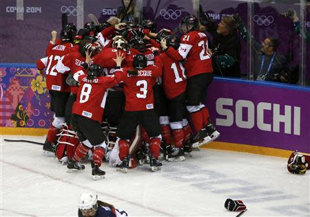 Canada's players celebrate after defeating Team USA to win their women's ice hockey gold medal game at the Sochi 2014 Winter Olympic Games