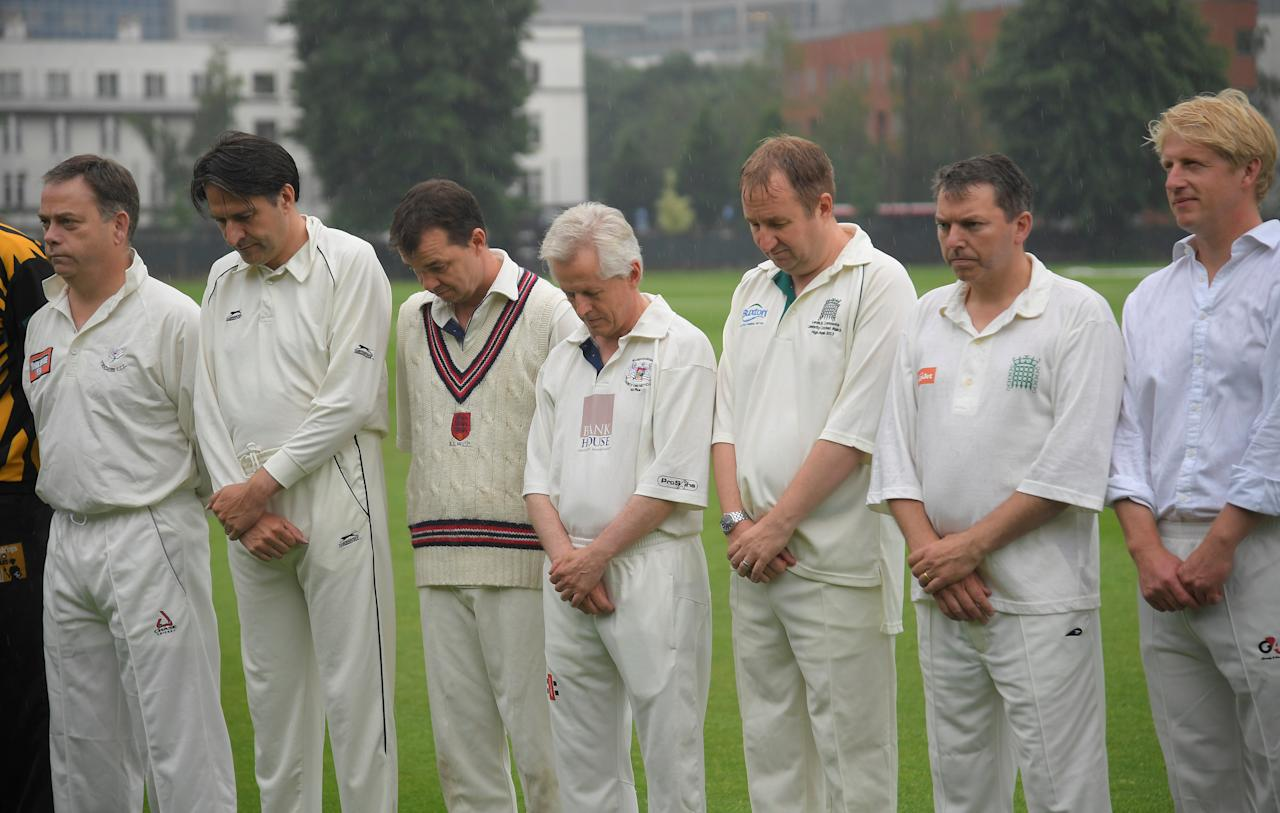 British lawmakers including MP Nigel Adams (L) and Jo Johnson (R) stand for a minute of silence, ahead of a charity cricket match against former international cricket players to remember and support the victims of the Grenfell Tower fire in London, Britain June 27, 2017. REUTERS/Toby Melville