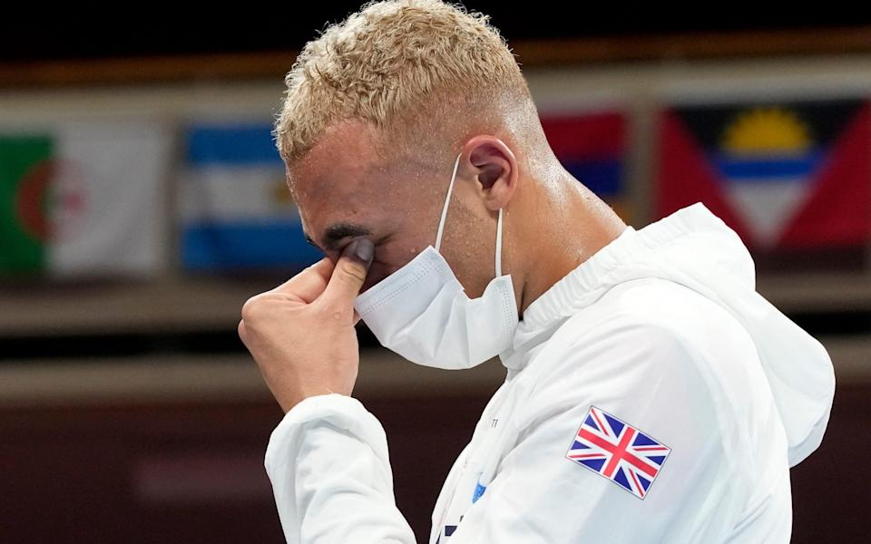 Silver Medalist Benjamin Whittaker, of Great Britain, rubs his eyes during the medal ceremony for the light heavy weigh - AP