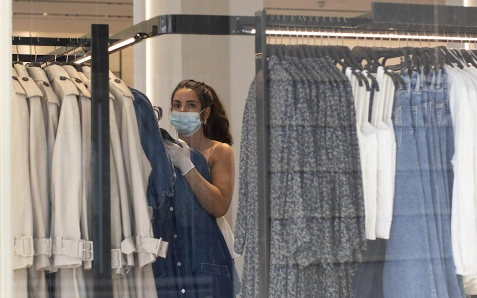 A worker changes clothes rails in a store on Oxford Street on May 19, 2020 in London, England. As shops gear up to open after a long period of closure, clothing stores are beginning to prepare to open their doors, and analysts have suggested that big discounts could be on offer as out of season stock is cleared. The British government has started easing the lockdown it imposed two months ago to curb the spread of Covid-19, abandoning its 'stay at home' slogan in favour of a message to 'be alert', but UK countries have varied in their approaches to relaxing quarantine measures - Dan Kitwood/Getty Images
