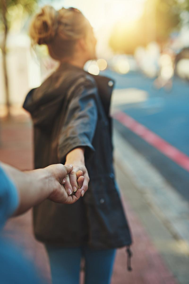 Shot of a young woman pulling on her boyfriend's hand