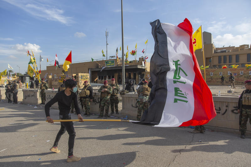 A man waves the Iraqi flag while the Iraqi army soldiers are deployed in front of the U.S. embassy, in Baghdad, Iraq, Wednesday, Jan. 1, 2020. Iran-backed militiamen have withdrawn from the U.S. Embassy compound in Baghdad after two days of clashes with American security forces. (AP Photo/Nasser Nasser)
