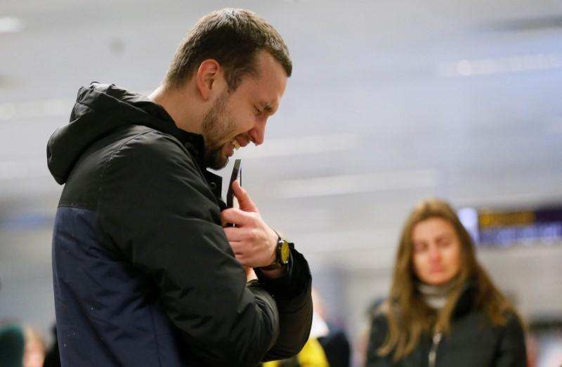 A relative of the flight crew member of the Ukraine International Airlines Boeing 737-800 plane that crashed in Iran, mourns at the Boryspil International airport