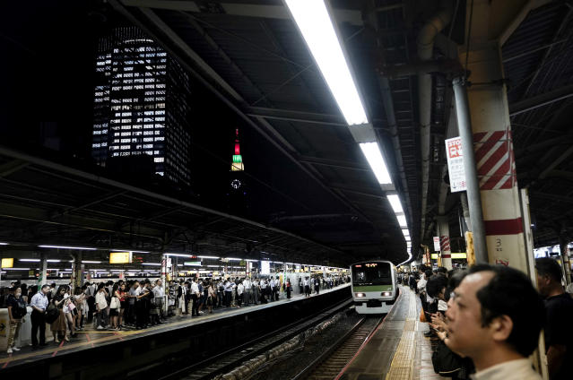 In this July 30, 2019, photo, commuters wait for trains to arrive during evening rush hours at Shinjuku Station in Tokyo. Tokyo has one of the most advanced public transport systems in the world, but with less than one year to go before the city hosts the 2020 Olympic Games, local governments, companies and commuters are bracing for unprecedented strain the events could put on rail transit and highways. (AP Photo/Jae C. Hong)