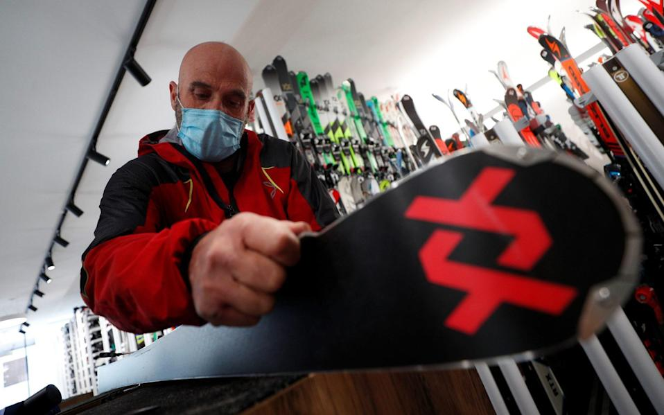 Giordano Callegari, 59, does maintenance work on a pair of skis at his ski rental at the ski resort of Passo Tonale - REUTERS