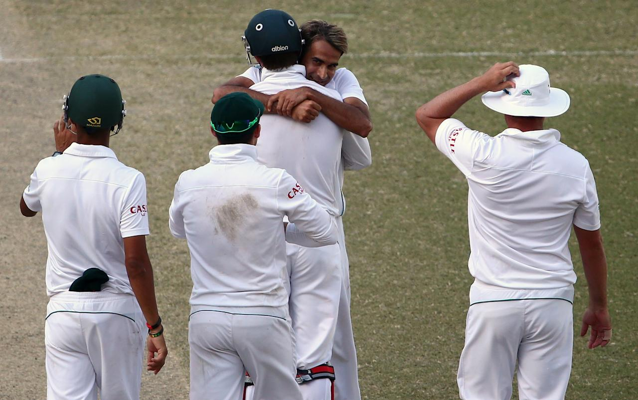 Bowler Imran Tahir (C) celebrates with his teammates after taking the wicket of Saeed Ajmal of Pakistan during the fourth day of the second Test cricket match between Pakistan and South Africa in Dubai on October 26, 2013. AFP PHOTO/MARWAN NAAMANI        (Photo credit should read MARWAN NAAMANI/AFP/Getty Images)