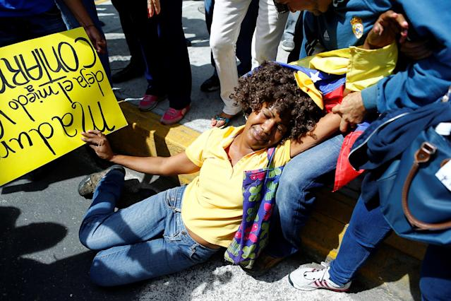 <p>An opposition supporter simulates a faint for hunger during a rally to demand a referendum to remove President Nicolas Maduro in Caracas, Venezuela, June 7, 2016. (Reuters/Ivan Alvarado) </p>