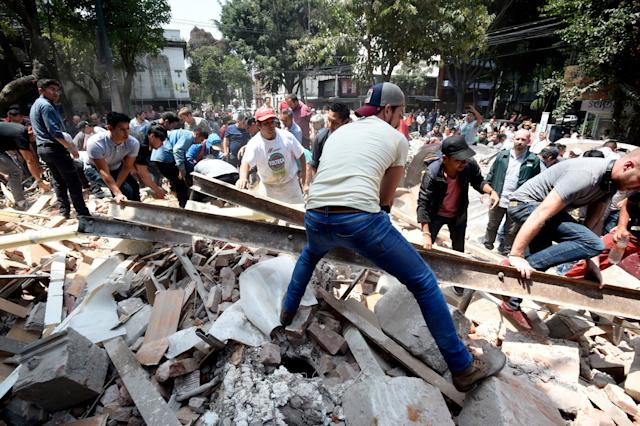 People remove debris of a collapsed building.