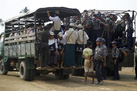 Volunteers and police board vehicles before proceeding to Rohingya refugee camps to collect data for the census in Sittwe