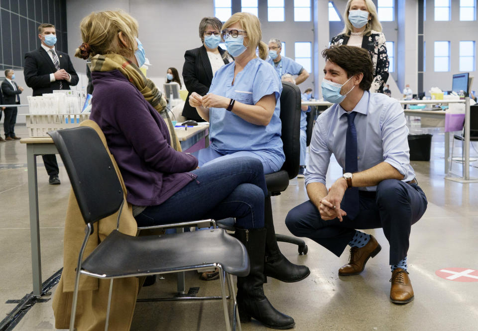 Canada's Prime Minister Justin Trudeau chats with a woman about to receive a COVID-19 vaccine while touring a vaccination clinic in Montreal on Monday, March 15, 2021. Canada once was hailed as a success story in dealing with the coronavirus pandemic, faring much better than the United States in deaths and infections because of how it approached lockdowns. But the trade-dependent nation has lagged on vaccinating its population because it has had to rely on the global supply chain. (Paul Chiasson/The Canadian Press via AP)