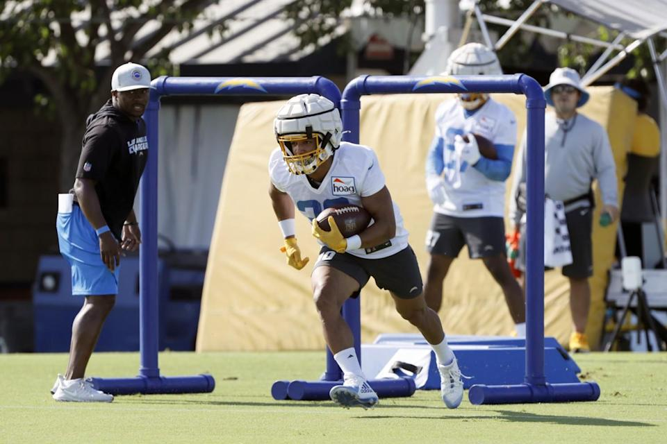 Chargers running back Austin Ekeler (30) runs in a drill while wearing a new protective practice helmet.