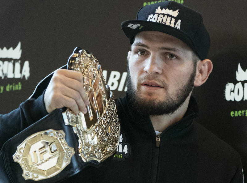 UFC lightweight champion Khabib Nurmagomedov holds the trophy belt during a news conference in Moscow, Russia, Monday, Nov. 26, 2018. The Russian professional mixed martial arts fighter Nurmagomedov, said he can imagine a reconciliation with Conor McGregor after the bitter feud around last month's title fight, but said he would like to fight Floyd Mayweather Jr. (AP Photo/Pavel Golovkin)