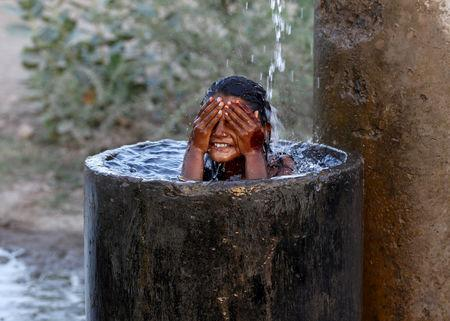 FILE PHOTO: A girl bathes to cool off herself with water that is leaking from a broken pipe valve on a hot summer day on the outskirts of Ahmedabad, India, May 18, 2015. REUTERS/Amit Dave/File Photo