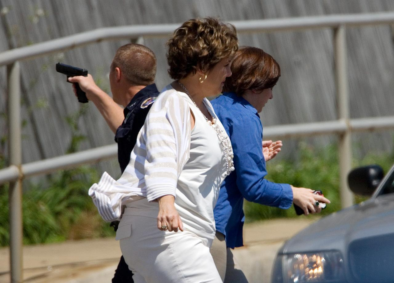 Police escort two women away from the Prudential Executive Group Real Estate office in Valparaiso, Ind. after a standoff Friday, May 25, 2012, where a gunman was holding an unknown number of hostages before shooting himself twice in the head. Police say the gunman held employees hostage inside the building for several hours before releasing the last two unharmed. (AP Photo/The Times of Northwest Indiana, Jon L. Hendricks)