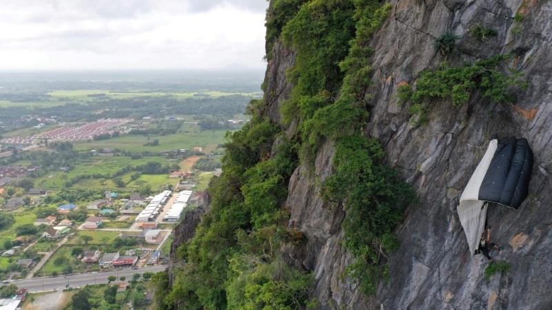 BASE jumper hangs from his parachute at Khao Thalu cliff in Phatthalung