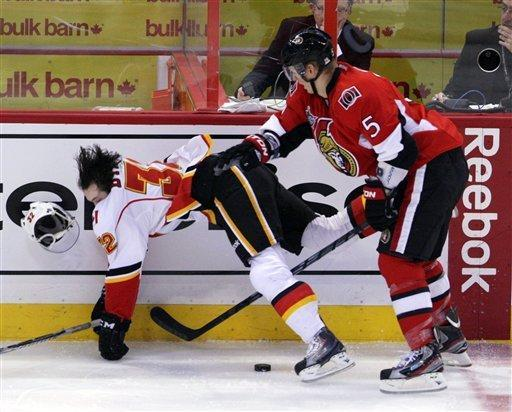 Calgary Flames' Paul Byron (32) is checked by Ottawa Senators' Brian Lee (5) during first-period NHL hockey game action in Ottawa, Ontario, Friday, Dec. 30, 2011. (A{P Photo/The Canadian Press, Fred Chartrand)