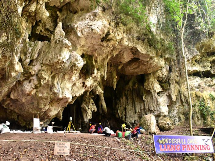 """a picture shows a cave in a protruding rugged cliff of white stone. A sign reads: """"Wonderful cave, Liang Panninge""""."""
