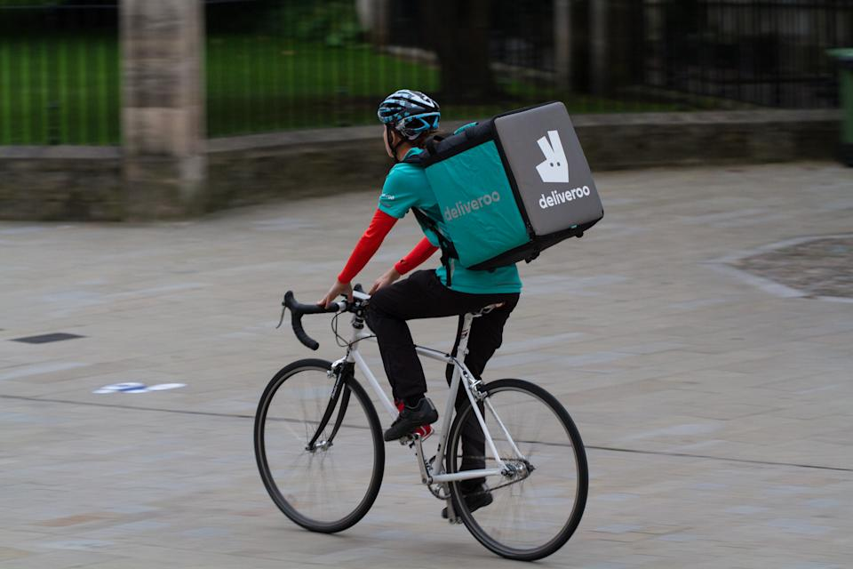 York, UK - September 19, 2016. A take away delivery cyclist from the increasingly popular hot food delivery company called Deliveroo speeding through city streets to deliver food to people's homes.