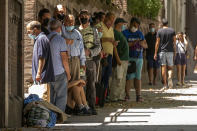 People queue to receive donated food in Madrid, Spain, Thursday, Aug. 5, 2021. Food requests have increased considerably in the last months due to the coronavirus pandemic. (AP Photo/Andrea Comas)