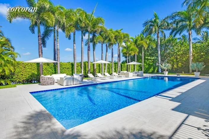 """<div class=""""caption""""> The pool shaded by towering palm trees in Epstein's Palm Beach estate. </div> <cite class=""""credit"""">Courtesy of The Corcoran Group</cite>"""