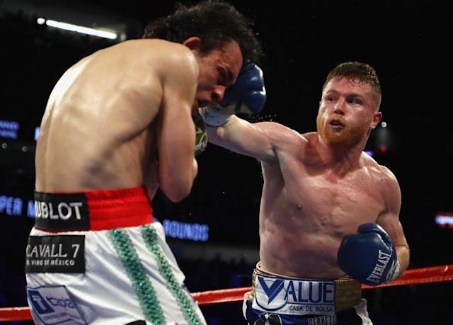 Canelo Alvarez (R) punches Julio Cesar Chavez Jr. during fight on Saturday. (Getty)
